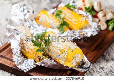 Grilled corn cobs on wooden plate - stock photo