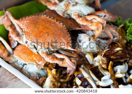 Grilled crabs and squids on a table