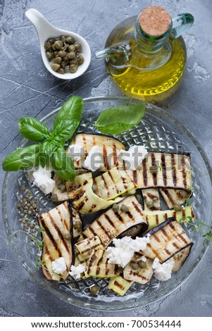 Grilled Eggplant And Zucchini With Olive Oil, Capers And Cheese On A Grey  Stone Background