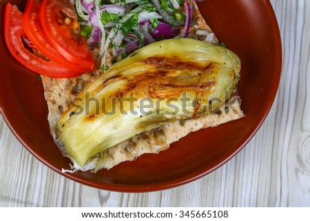 Grilled eggplant with bread, tomato, onion rings and salad leaves - stock photo