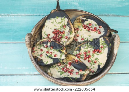 grilled eggplant with tahini and pomegranate seeds - stock photo
