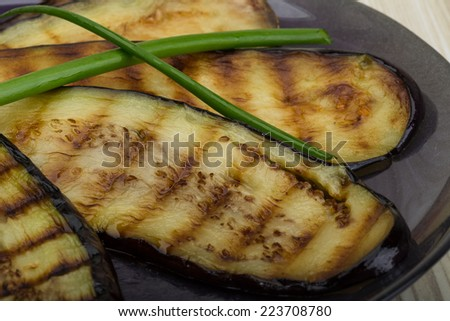 Grilled eggplants in the plate on wooden background - stock photo