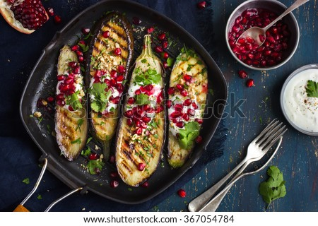 grilled eggplants with garlic yogurt sauce, walnuts and pomegranate, top view - stock photo