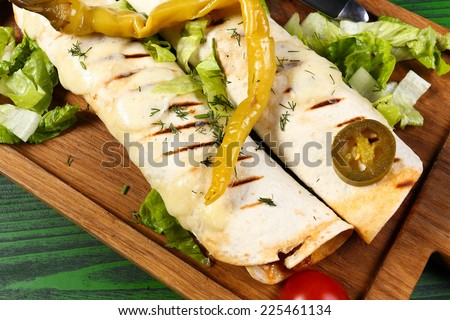 Grilled enchiladas with meat, vegetables and jalapeno pepper on wood board closeup - stock photo