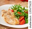 grilled fillet of chicken and a salad of arugula and tomato - stock photo
