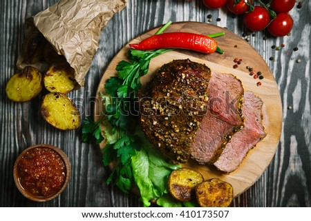 Grilled fillet steak beef served with tomatoes and roast vegetables on an old wooden board