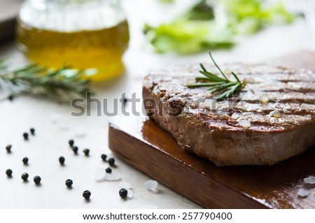 Grilled fillet steak on wooden cutting board - stock photo