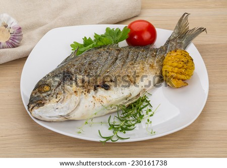 Grilled fish - dorado with herbs on the desk
