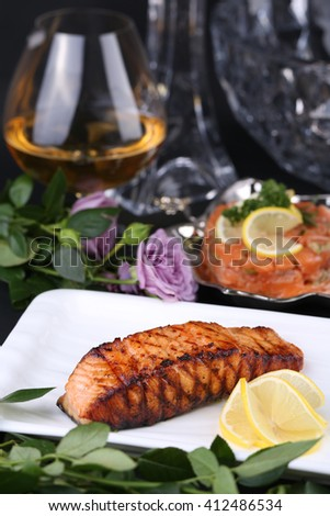 Grilled fish fillet on barbecue with lemon against the backdrop of a wine glass, salad salmon  and flowers - stock photo