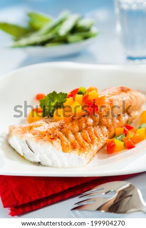 Grilled fish fillet served with colorful diced sweet peppers for a delicious seafood lunch - stock photo