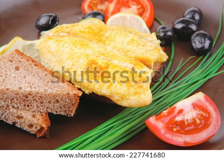grilled fish fillet served with tomatoes,olives and bread . no people. shallow dof - stock photo