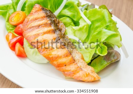 Grilled fish fillet with fresh salad served on the plate - stock photo