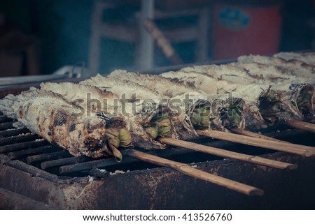 Grilled fish for sale at the Thai street food market , process in vintage style