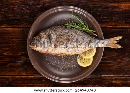 Grilled fish on brown plate with herbs and lemon on old wooden background, top view. Mediterranean luxurious seafood concept. - stock photo