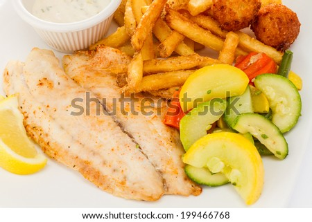 Grilled fish served with french fries, vegetable medley, and hush puppies. - stock photo