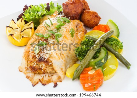 Grilled fish served with vegetable medley and hush puppies. - stock photo