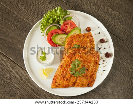 Grilled fish tikka served on a plate with salad and tarter sauce top aerial shot - stock photo