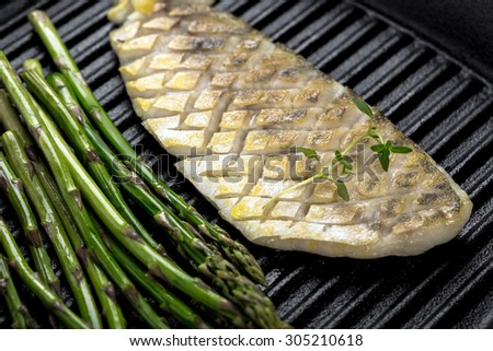 grilled fish with green asparagus on frying pan - stock photo