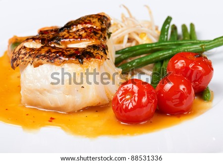 grilled fish with runner beans and cherry tomatoes on white plate - stock photo