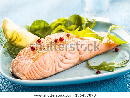 Grilled fresh salmon steak showing the texture of the flesh served with a wedge of lemon and rocket and leafy green salad - stock photo