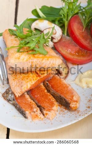 grilled fresh samon filet with vegetables salad tomato arugula mushroomsand paprika on top - stock photo