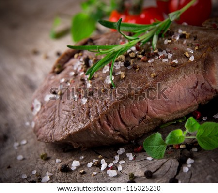 Grilled 500g bbq steak on wooden table - stock photo