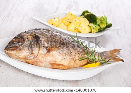 Grilled gilt head sea bream on plate  with lemon and rosemary and potatoes. Mediterranean bright seafood background. - stock photo