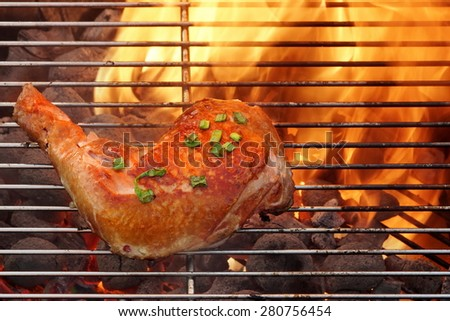 Grilled Glazed Chicken Quarter On The Hot BBQ Charcoal Flaming Grill Close-up. - stock photo