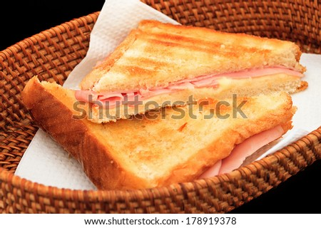 Grilled ham and cheese sandwich in a basket on a black background - stock photo
