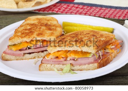 Grilled ham and cheese sandwich with pickles on a plate