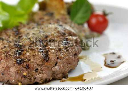 grilled hamburger on a plate with salad - stock photo