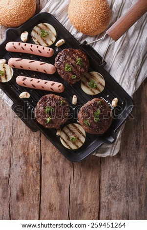 grilled hamburgers and hot dogs on the grill pan. vertical top view