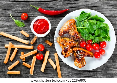 grilled Hot and spicy chicken wings with sesame seeds on a white dish with tomato sauce, fresh spinach salad, cherry tomatoes and bread sticks on an old wooden table, top view - stock photo