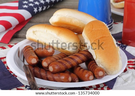 Grilled hot dogs and buns on a plate with american flag in background - stock photo