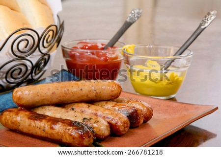 Grilled hot dogs on a stacked on a plate ready to serve with condimaents ketchup and mustard and buns  ready - stock photo