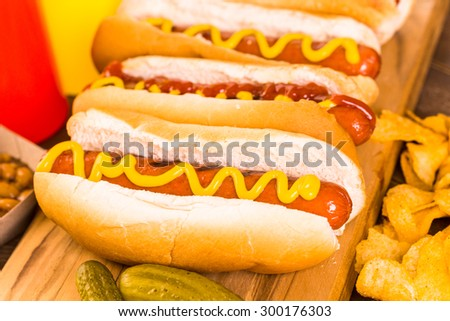 Grilled hot dogs on a white hot dog buns with mustard and ketchup.