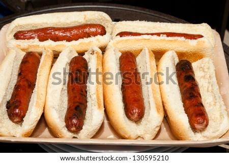 Grilled hot dogs with buns on a tray ready to pick up. - stock photo