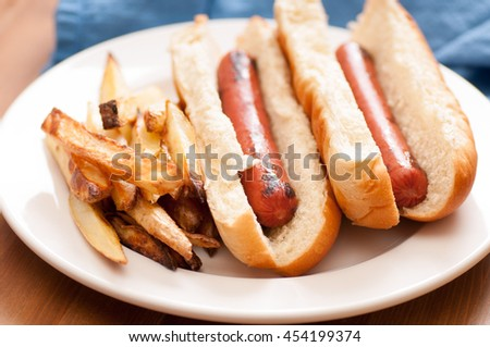 grilled hotdogs on white bread bun and home made fries. This is a classic lunch meal. - stock photo