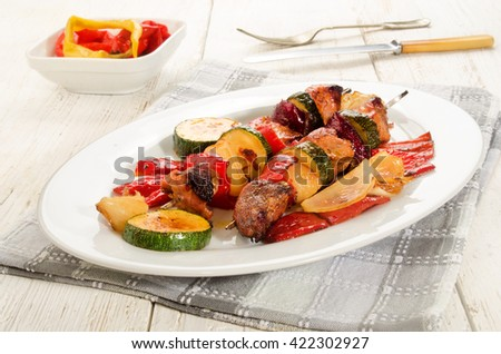 grilled hungarian pork, red pepper, onion and courgette skewers on an white oval plate