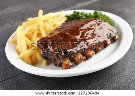 Grilled juicy barbecue pork ribs in a white plate with fries and parsley. - stock photo