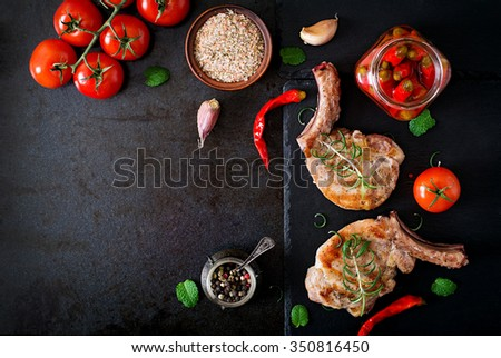 Grilled juicy steak on the bone with vegetables on a dark background. Top view - stock photo
