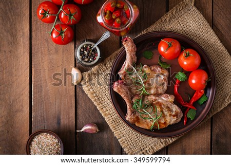 Grilled juicy steak on the bone  with vegetables on a dark wooden background. Top view - stock photo
