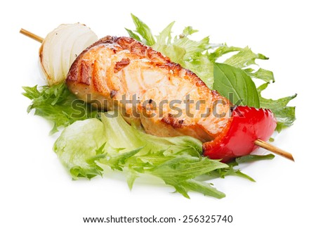 Grilled kebab from salmon with vegetable garnish on a plate