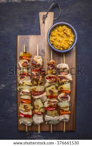 grilled kebabs with peppers, pork and pineapple on a cutting board with sauce on wooden rustic background top view close up - stock photo