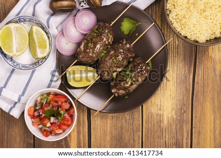Grilled kebabs with vegetable salad, couscous and seasonings over wooden table - stock photo