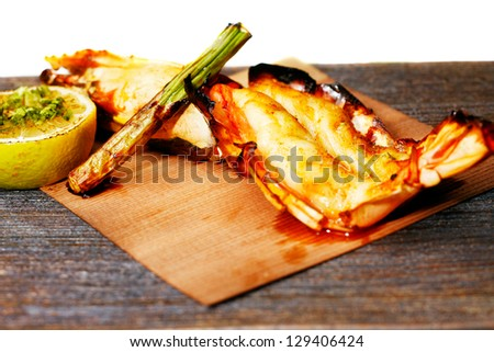 Grilled King Prawn Tikka with roasted asparagus and garnished with fresh lemon is an exotic rustic Indian recipe - stock photo