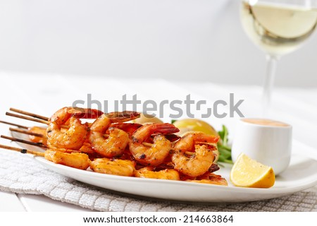 Grilled king prawns on skewers dish, with boiled potatoes and cocktail sauce, on white plate and a glass of white wine - stock photo