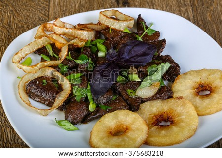 Grilled liver with onion rings and herbs