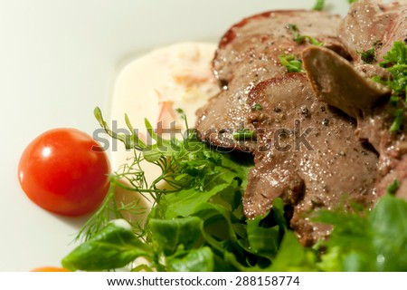 Grilled liver with salad, nice garnish on white plate, in a restaurant  - stock photo