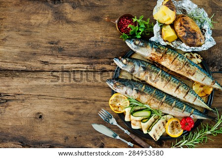 Grilled mackerel fish with baked potatoes on wooden table - stock photo